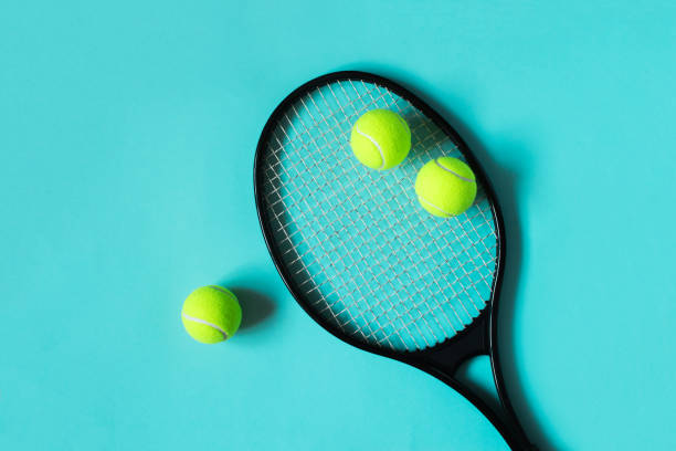 Tennis balls and racket on blue background. Sport equipment. Flat lay. stock photo