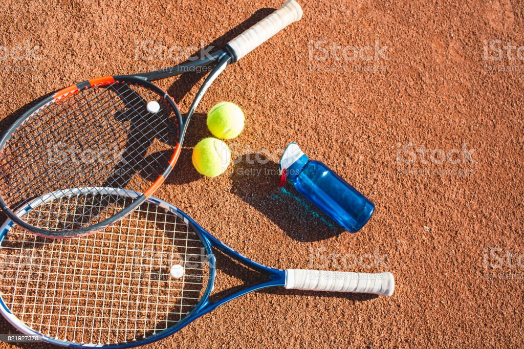 Tennis balls and rackets on the court stock photo