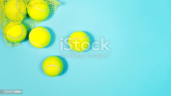Tennis balls close up on blue hard tennis court. Copy space, selective focus. Blue and yellow.