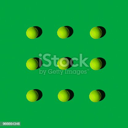 istock Tennis Balls in Pattern on a Green Background, Flat Layout 966664346