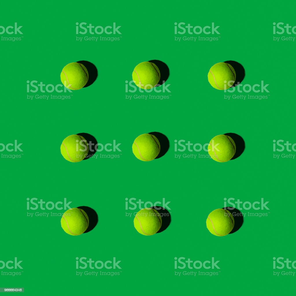 Tennis Balls in Pattern on a Green Background, Flat Layout stock photo