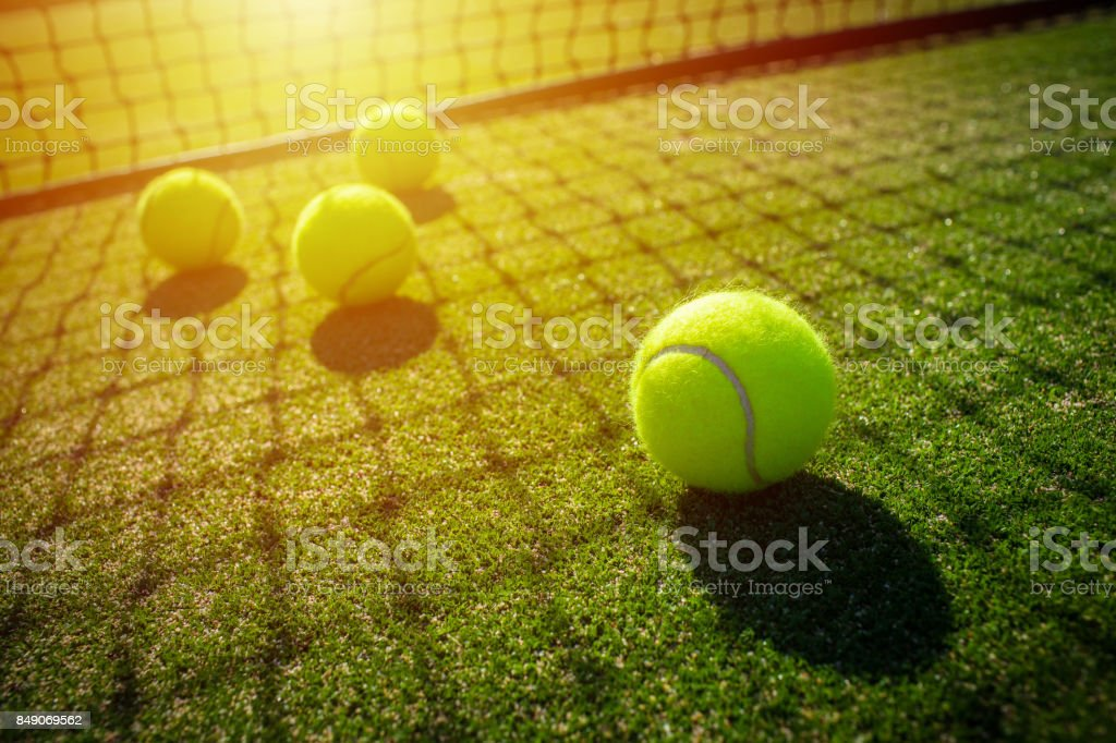 Tennis balls on grass court with sunlight stock photo