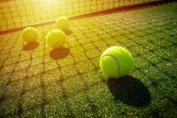 tennis balls on grass court with sunlight - tennis stock pictures, royalty-free photos & images