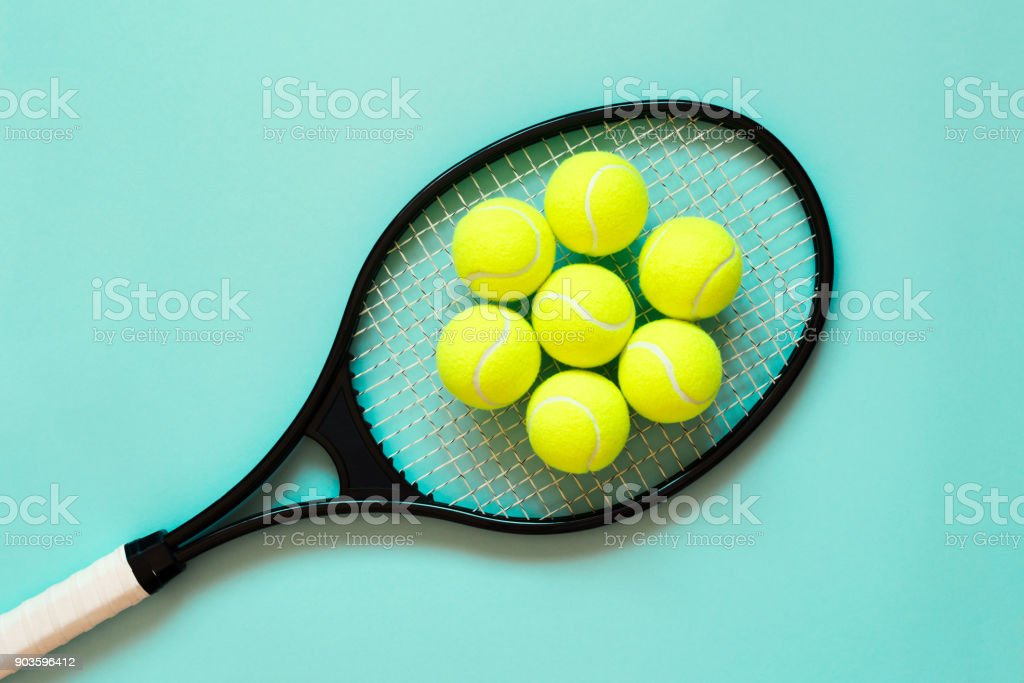 Tennis balls on racket. Blue background. Concept sport. Flat lay.