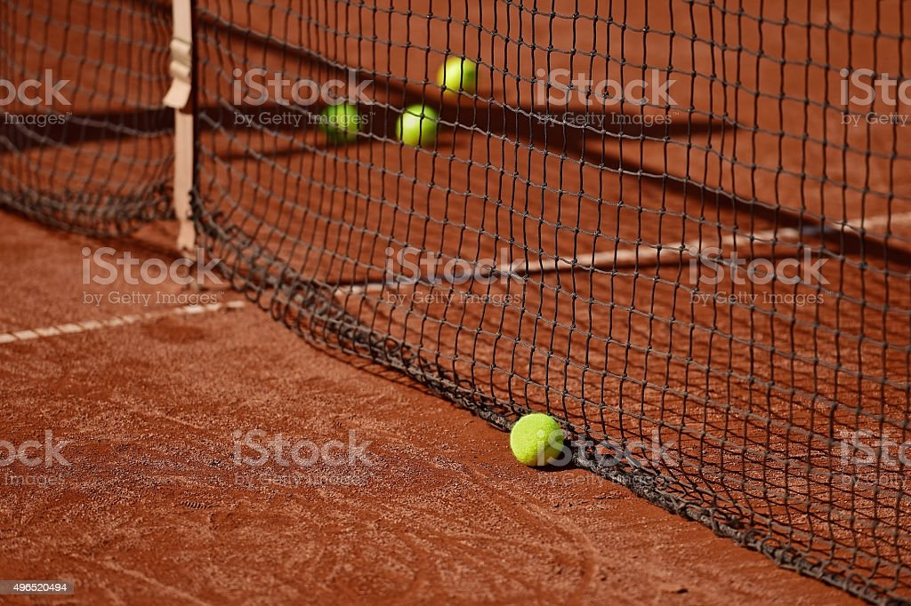 Detail shot with tennis balls close to the net on a tennis clay court