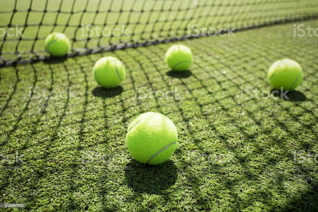 Tennis balls on the court grass stock photo