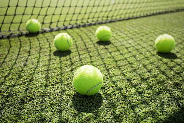 palle da tennis sul campo in erba - set tennis o pallavolo foto e immagini stock