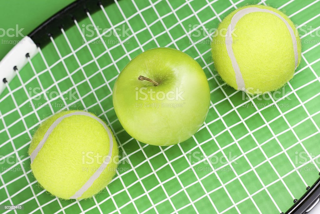 Tennis balls with apple and racket royalty-free stock photo