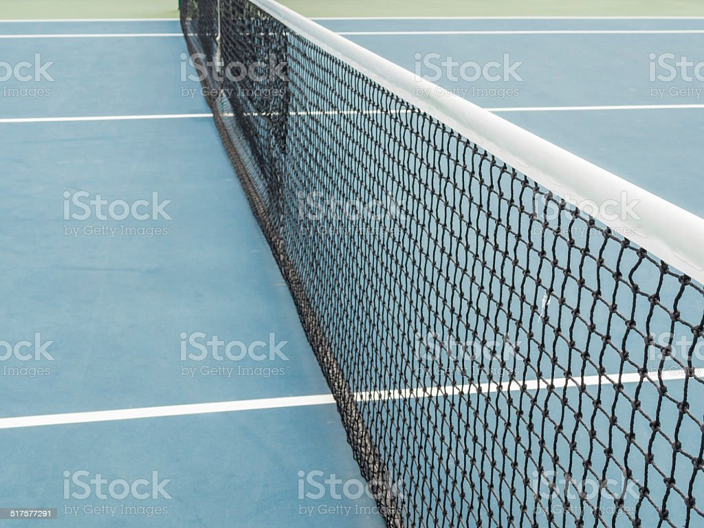 Tennis blue hard court with net in sunny day competition stock photo