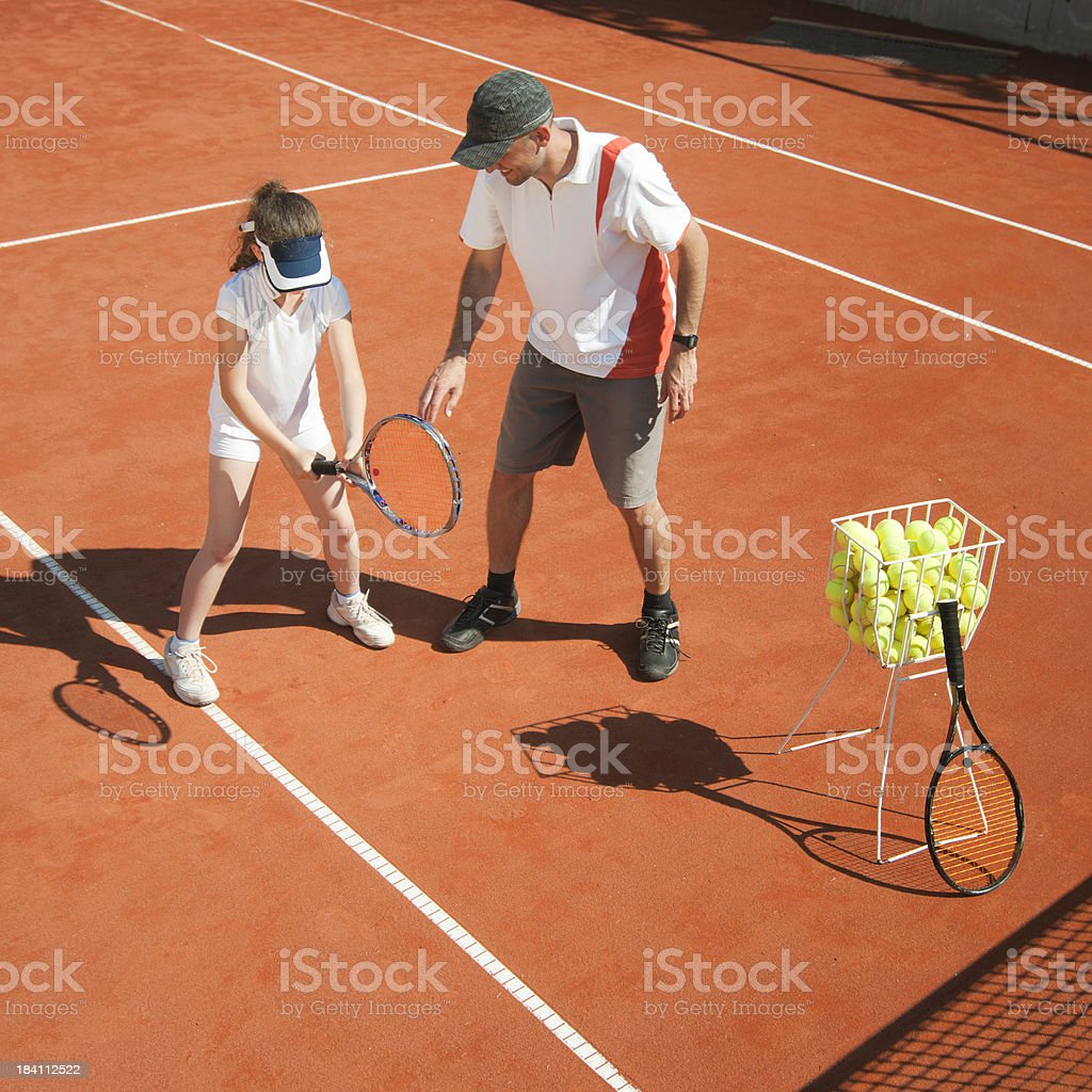 Tennis coach in class with young girl stock photo