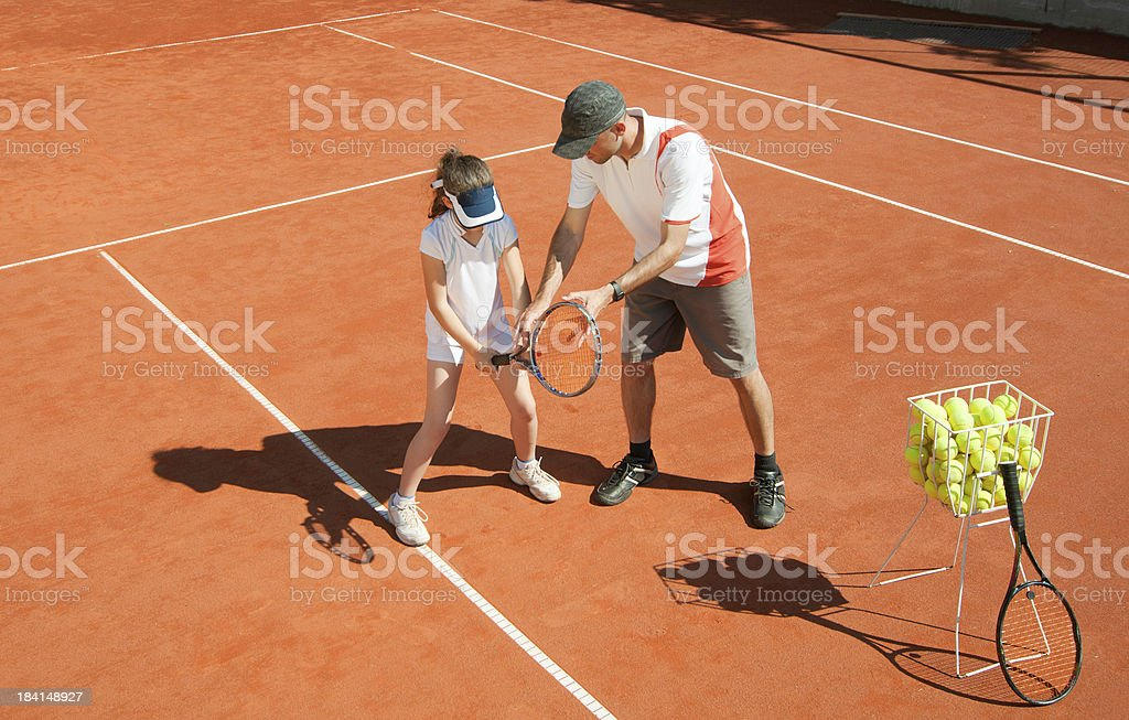 Tennis coach with talented young girl stock photo