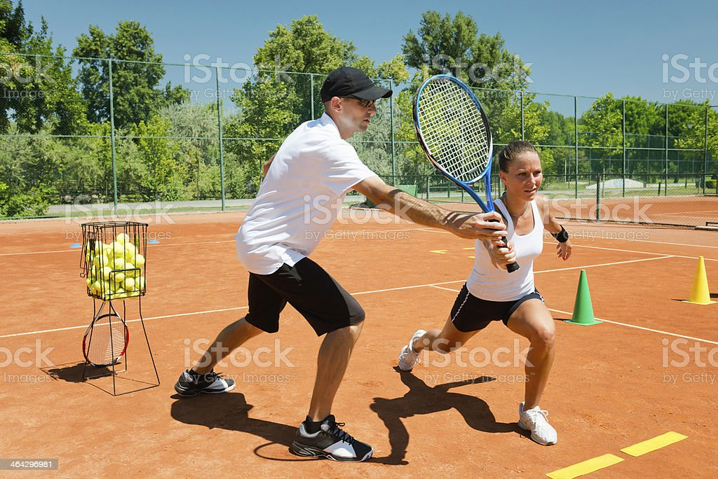 Tennis coach working with female student stock photo