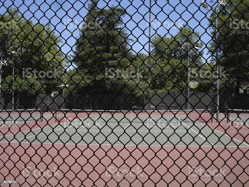 Tennis court behind fence royalty-free stock photo
