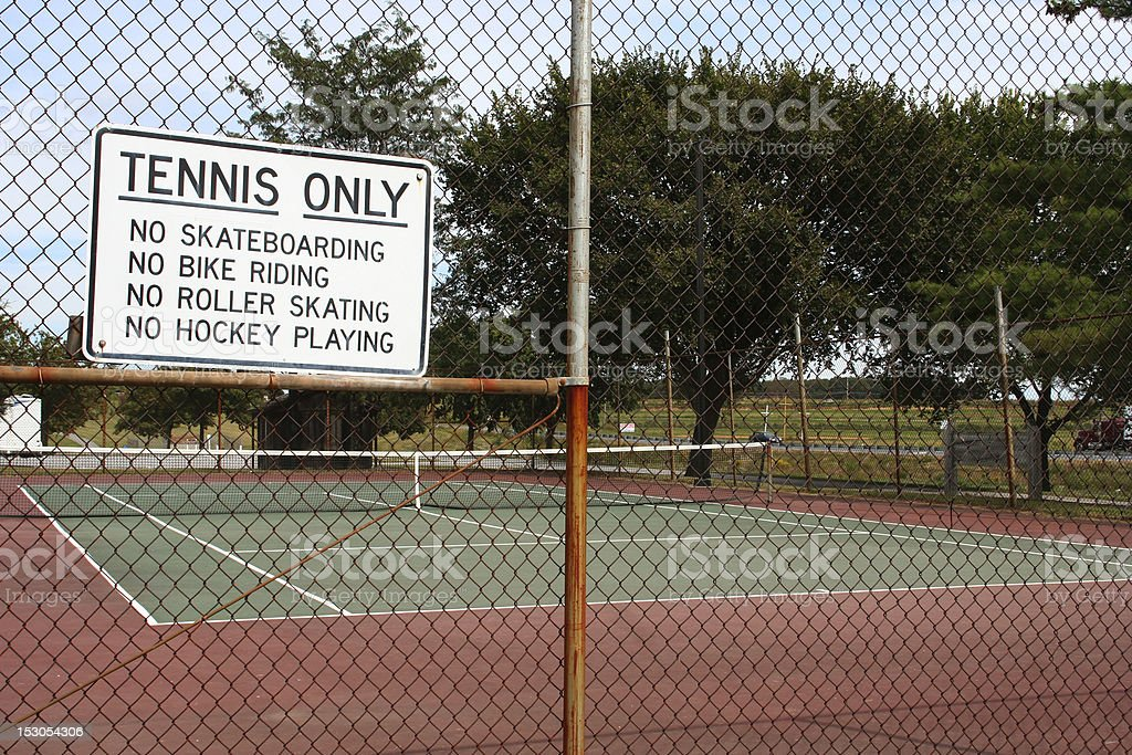 Tennis court in park with rules sign royalty-free stock photo