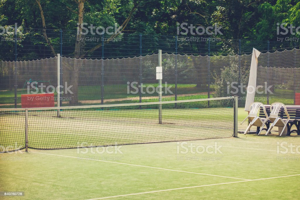 tennis court with green trees in background stock photo