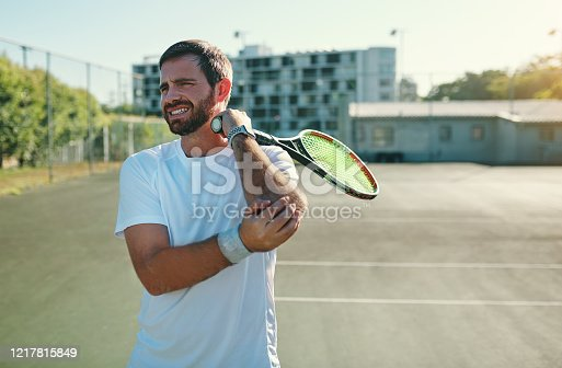 Shot of a sporty young man holding his elbow in pain while playing tennis on a tennis court