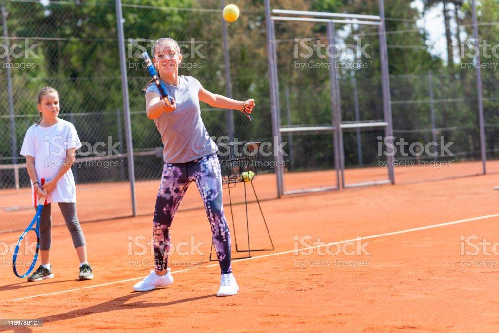 Two little girls playing tennis on orange tennis court