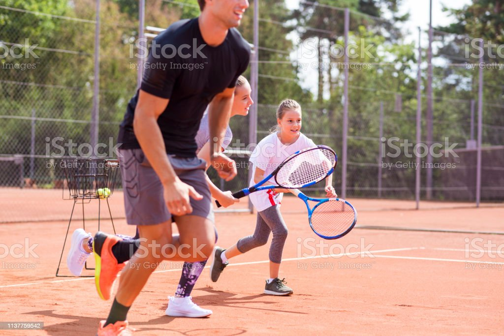 Two little girls and their tennis coach running at sand tennis court