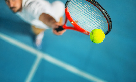 Closeup high angle view of two male tennis player competing in an outdoors night match. He's hitting a serve or a volley against blue hard court with copy space.