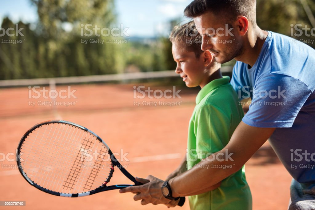 Tennis instructor assisting little boy on the tennis court. stock photo