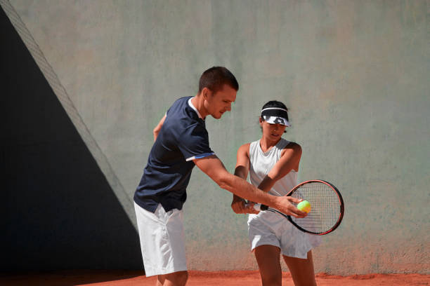 Tennis instructor giving lessons to young woman in tennis clay court stock photo