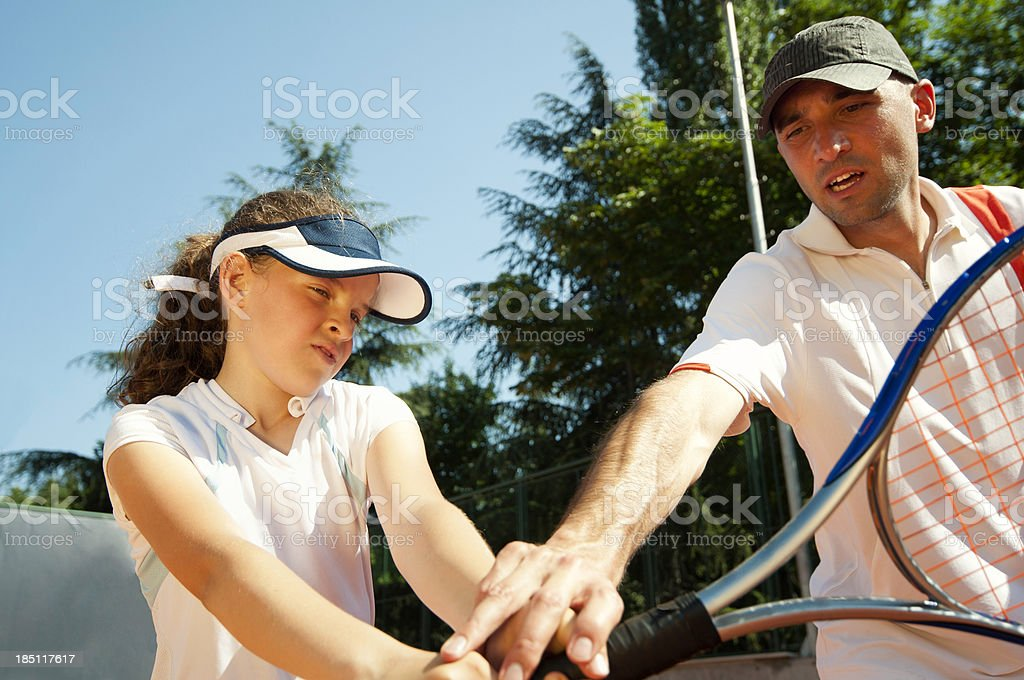 Tennis instructor teaching young talent stock photo