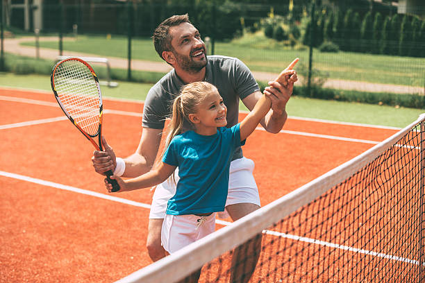 tennis is fun when father is near. - tennis stock pictures, royalty-free photos & images