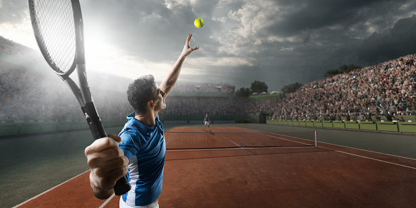 Male sportsman is playing tennis on an outdoor stadium full of spectators. He is wearing unbranded sports cloth and using unbranded sport equipment