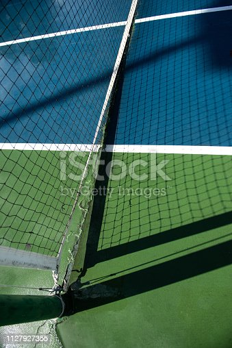 A brief moment of sunshine after a storm casts a very clear and detailed shadow of the net on a damp tennis court.