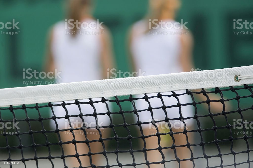 tennis net with the back of two female players royalty-free stock photo