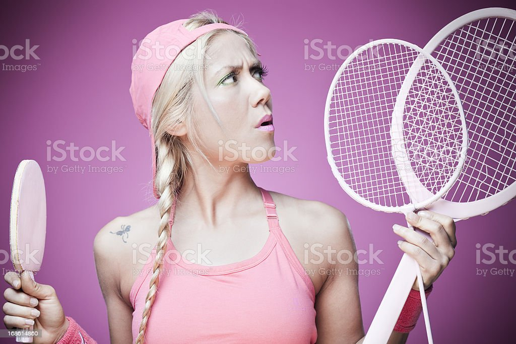 Tennis or ping pong? girl in doubts. stock photo