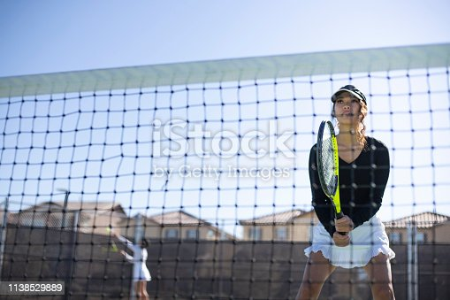 Two girls playing tennis on a sunny day.