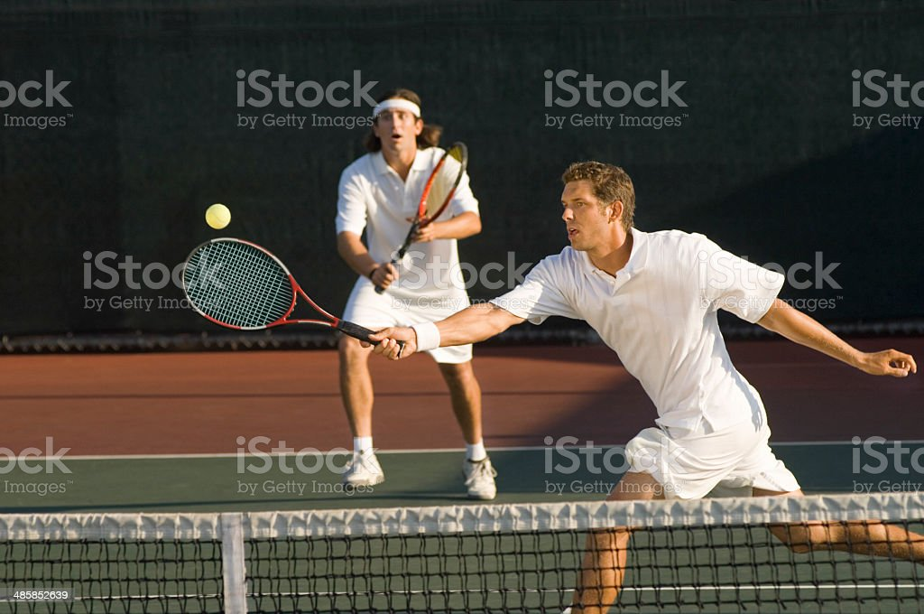 Tennis Player Hitting Ball With Doubles Partner Standing In Back stock photo
