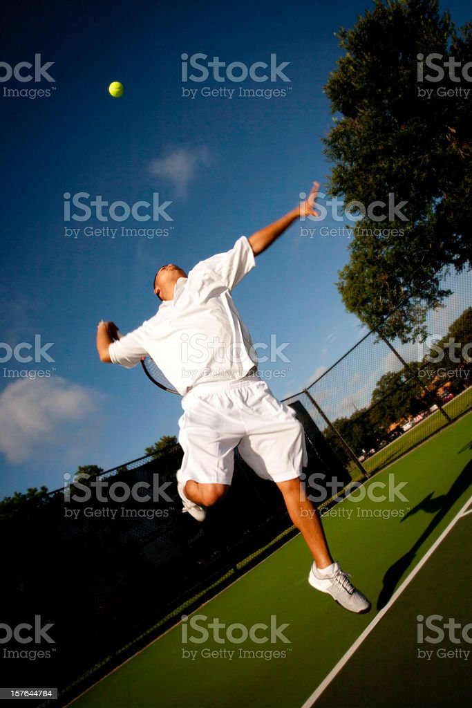 Tennis Player in Mid Serve on a Deep Blue Sky royalty-free stock photo