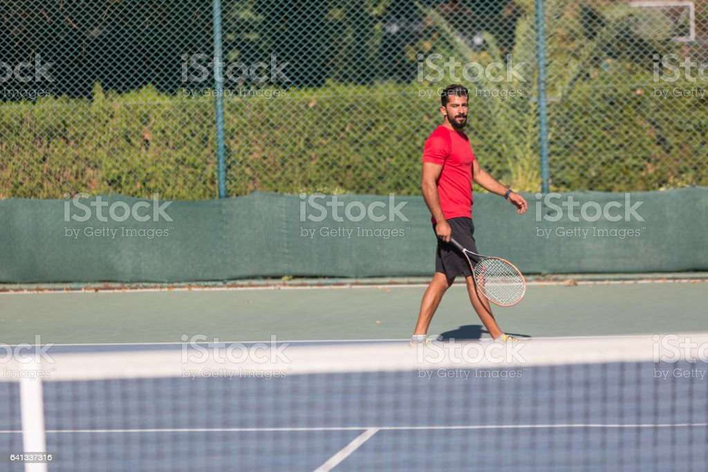 Tennis player man hitting ball in a volley. Male sport fitness...