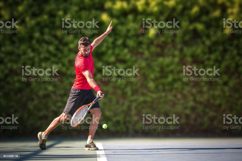Tennis player man hitting ball in a volley. stock photo