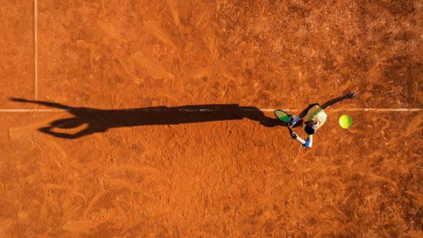 joueur de tennis sur le service sur la cour de terre battue - tennis photos et images de collection