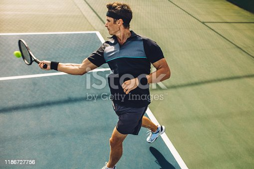 Pro tennis player hitting forehands on a hard court. Professional tennis player practicing on a hard court.
