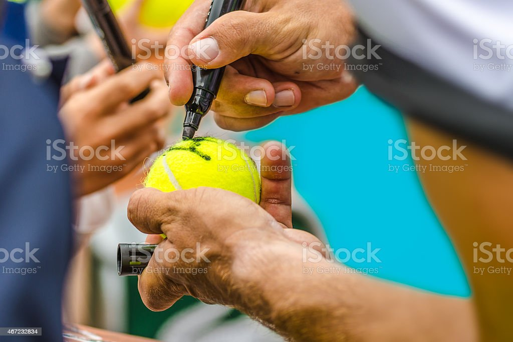 Tennis player signing autograph on a ball stock photo