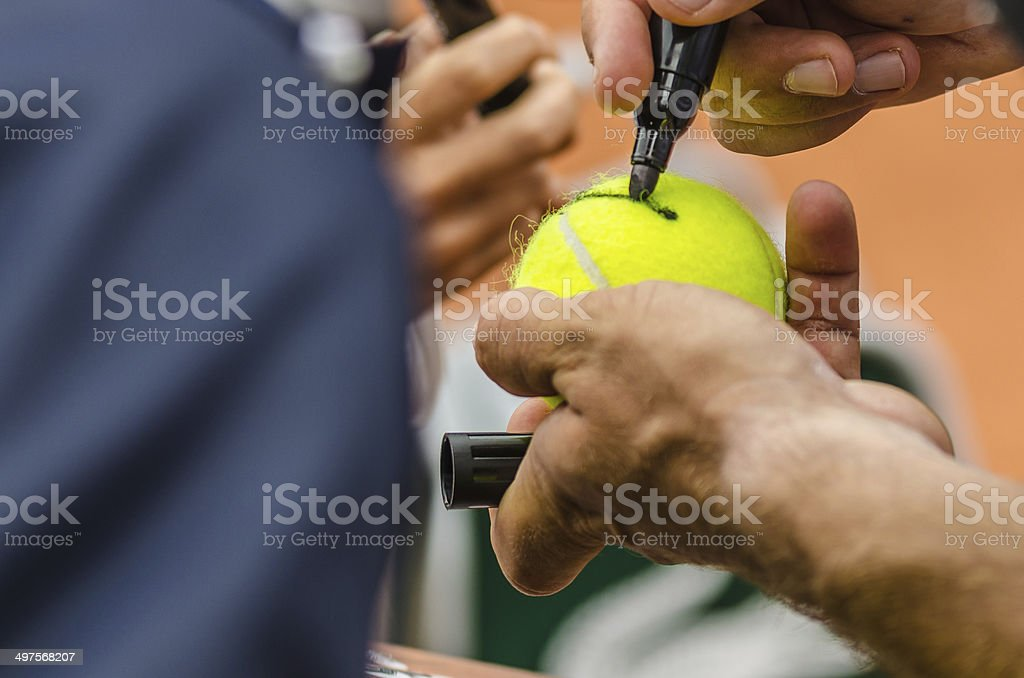 Tennis player signs autograph after win stock photo