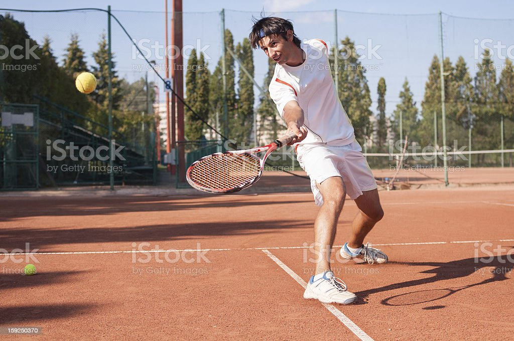 tennis player sliding after a dash for short ball stock photo