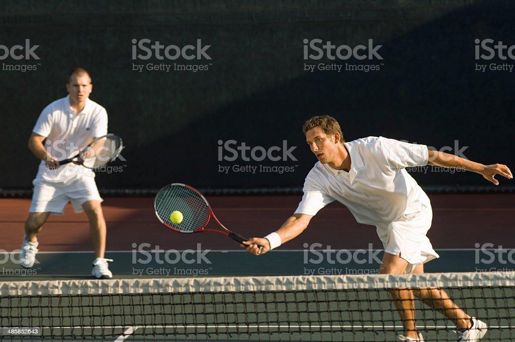 Tennis Player Swinging at Ball stock photo