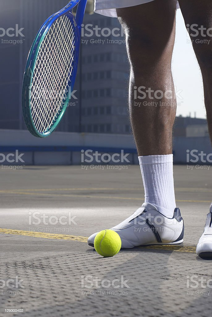 Tennis player with ball on rooftop court royalty-free stock photo