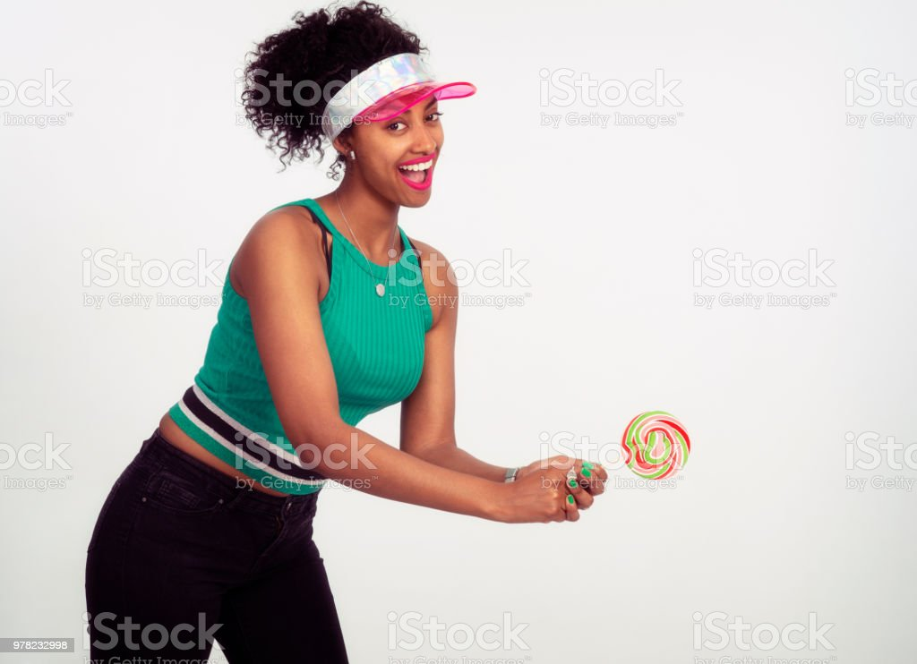 Tennis player woman holding sweet swirl wheel lollipop. stock photo