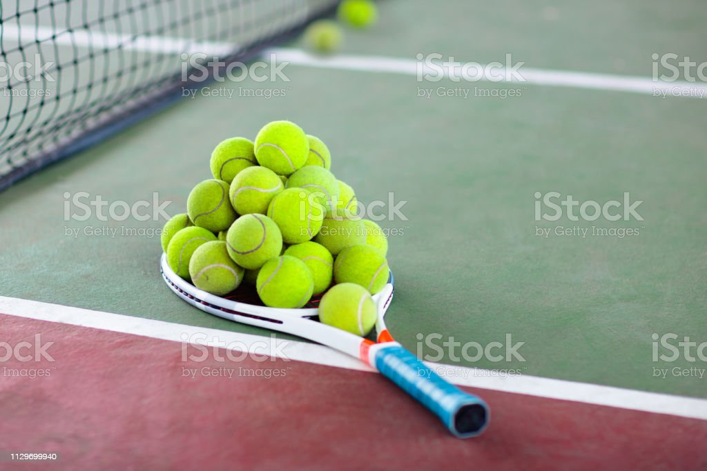 Tennis racket and ball on court after game. stock photo