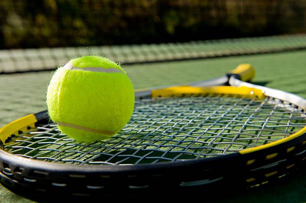 tennisschläger und ball auf gericht - filzkugeln stock-fotos und bilder