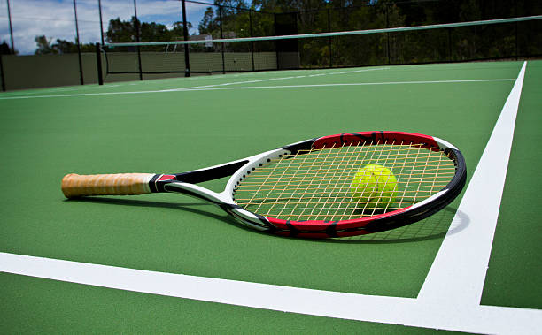Tennis racket and ball sitting on empty court stock photo