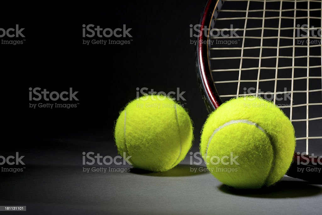 Tennis racket and balls on dark background royalty-free stock photo