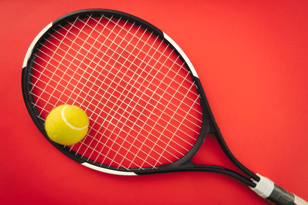 Tennis racket and tennis ball on the red clay court stock photo