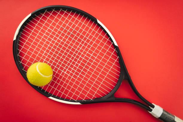 Raquette de tennis et balle de tennis sur le court en terre battue rouge - Photo